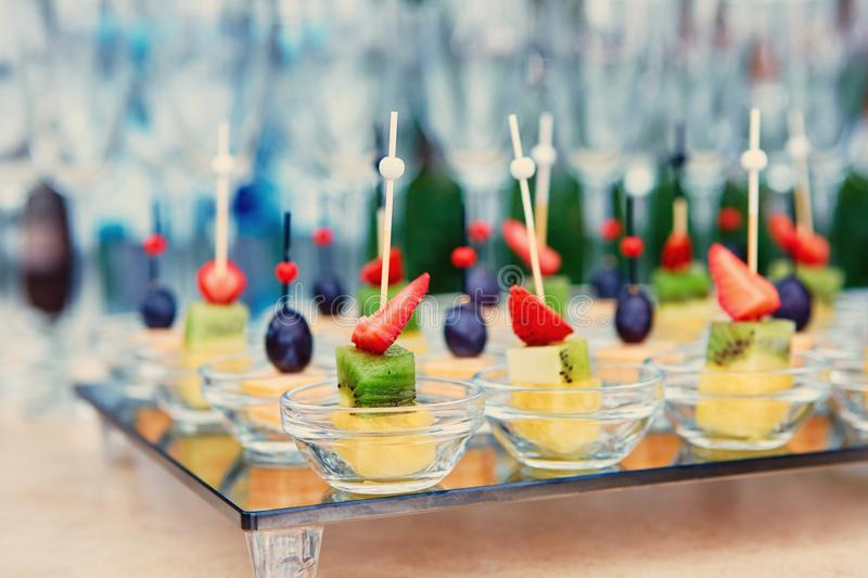 Fruit canapes on a glass tray, on the background of wine glasses and champagne. Catering concept stock photos