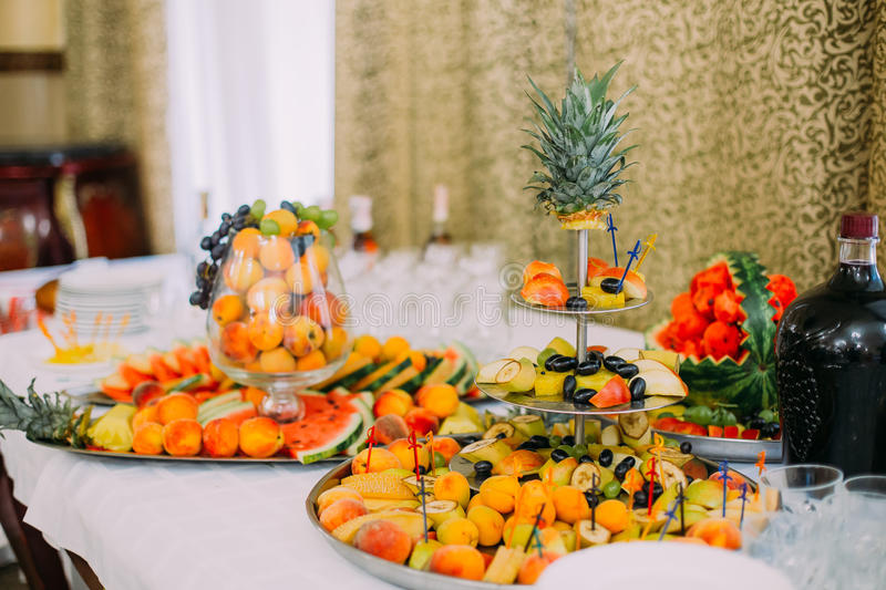 Fruit catering table with fresh juicy bananas, apples, pineapples, grapes, water melon and peaches in glass vase royalty free stock image