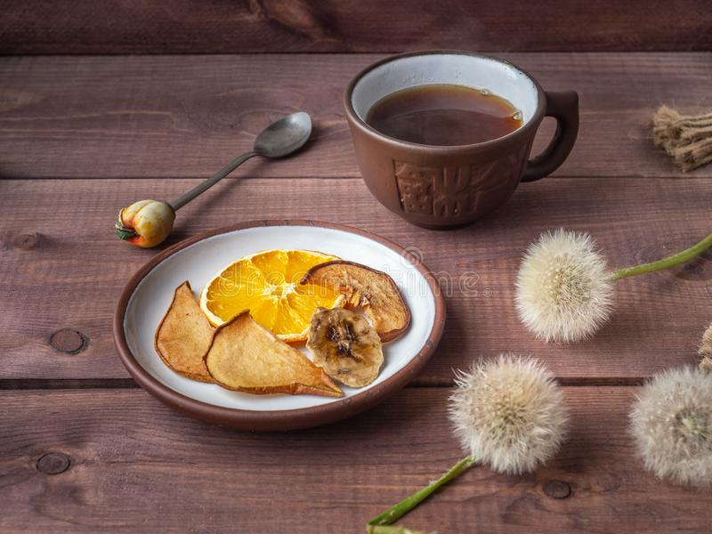 Fruit chips, healthy snack with morning coffee in a brown ceramic mug on a wooden rustic tray stock photos