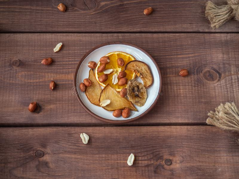 Fruit chips without sugar and additives on a small plate and peanuts, the plate is on a wooden tray, for a healthy snack stock photography