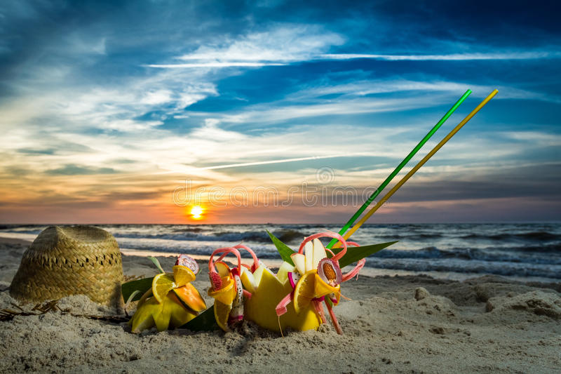 Fruit cocktail on the beach at sunset stock images