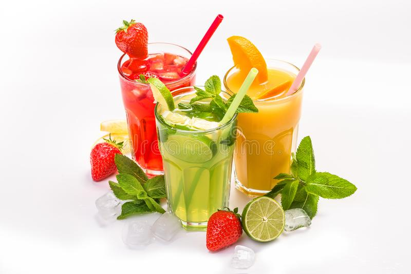 Fruit cocktail in glasses. Fruit drinks made of strawberry, orange, lime, lemon, decorated with mint royalty free stock photography