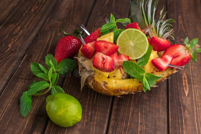 Fruit composition. Pineapple sliced in half with pineapple slices, strawberries and lime on a brown wooden background stock images