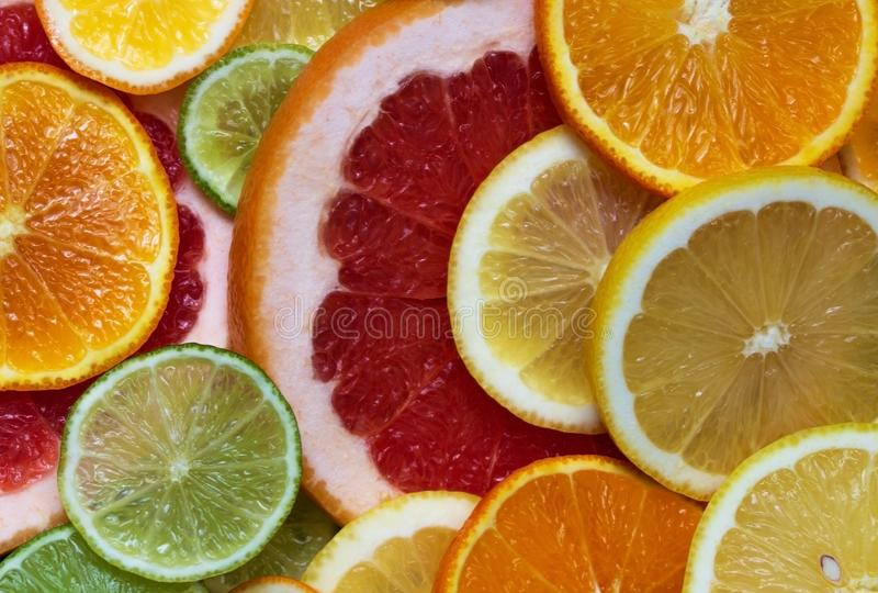 Fruit composition. Round colored slices of citrus. Green lime, yellow lemon, orange orange and red grapefruit sliced lie on the. Table close-up stock image