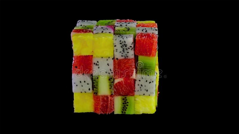 Fruit cube formed from small squares of assorted tropical fruit in a colorful arrangement including kiwifruit, strawberry, orange stock photo