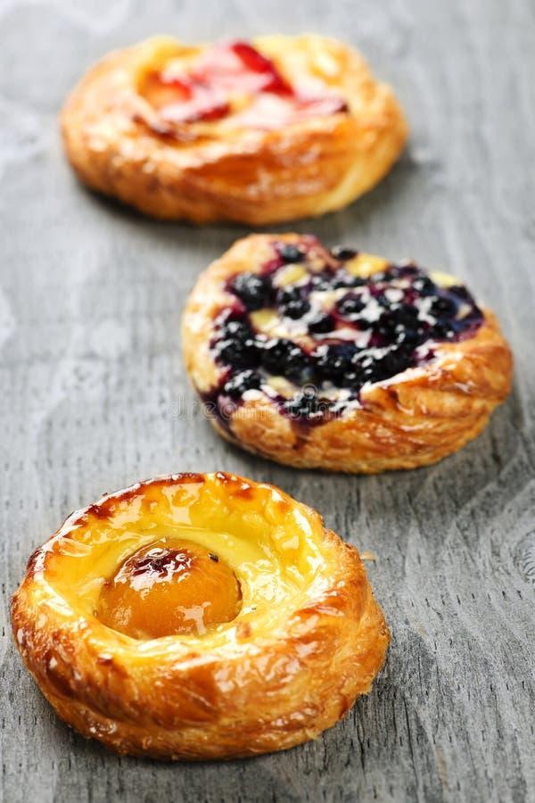 Fruit danishes. Closeup on three sweet fruit danish desserts stock photo