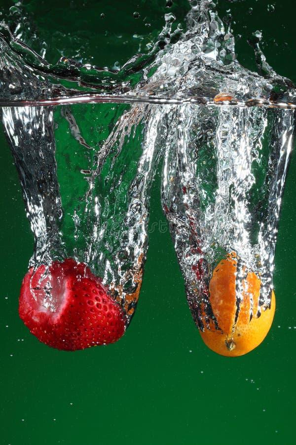 Fruit dat in water valt stock fotografie