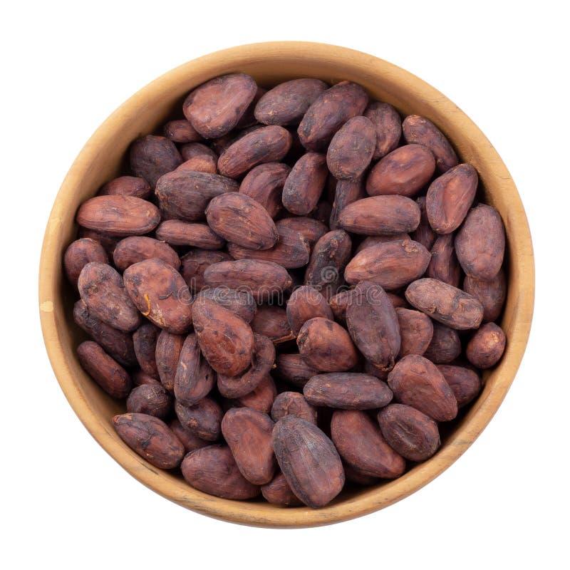 Fruit de cacao dans une cuvette en bois, haricots crus de cacao d'isolement sur un fond blanc images stock