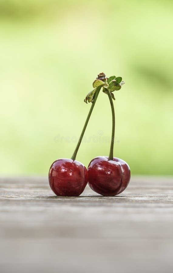 Fruit de cerise sur la table en bois au-dessus du fond de vert de bokeh image stock