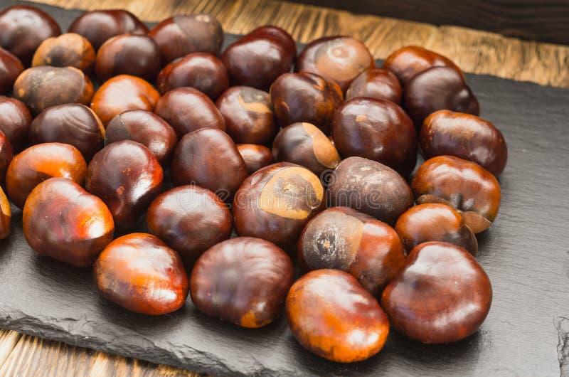 Fruit de châtaigne situé sur un plateau d'ardoise beaucoup tout autour sur le côté photo stock