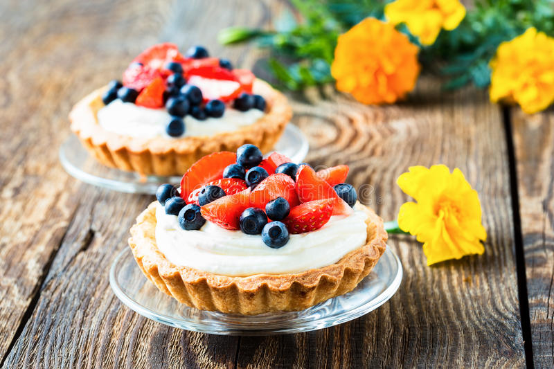 Fruit dessert tarts. With cream, strawberry, and blueberry on wooden table royalty free stock photos
