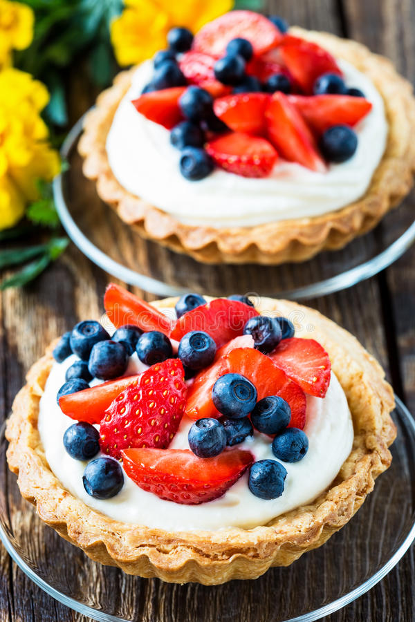 Fruit dessert tarts. With cream, strawberry, and blueberry on wooden table royalty free stock image