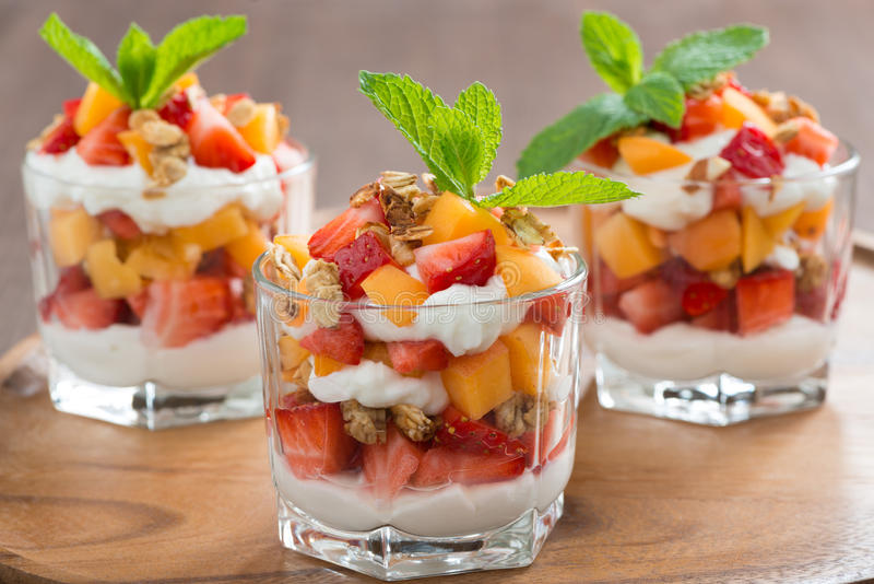 Fruit dessert with whipped cream and granola in a glass stock photography