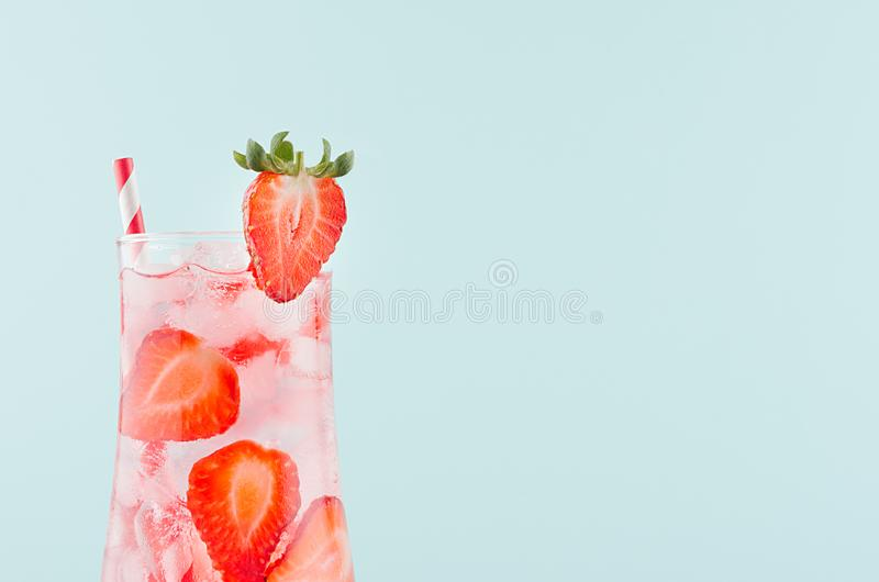 Fruit detox drink with red fruit slices, ice cubes, sparkling water, striped straw in misted glass on modern mint color background royalty free stock photo