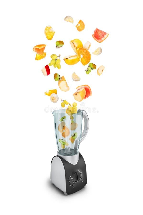 Fruit die in een juicer vallen royalty-vrije stock afbeeldingen