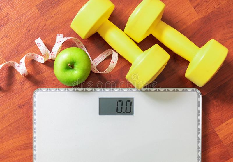 Fruit, dumbbell and scale, fat burn and weight loss concept. Diet royalty free stock photography