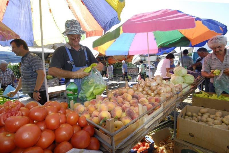 Fruit en plantaardige verkopers bij de markt stock afbeeldingen