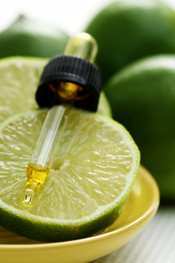 Fruit essence. Bottle of essence oil with fresh limes - beauty treatment stock image