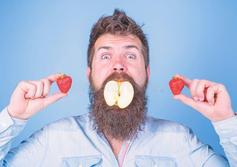 Fruit filling. Man handsome hipster long beard eat apple hold strawberry. Hipster surprised enjoy fruit filling. Man royalty free stock photography