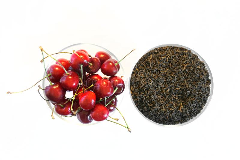 Fruit flavor. Black tea and ripe red sweet cherry on a white background. View from above royalty free stock images