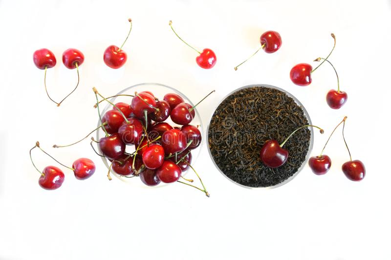 Fruit flavor favorite drink. Traditional black tea next to a red sweet cherry on a white background stock photos