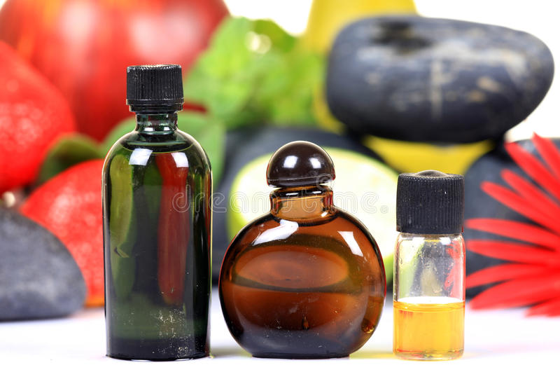 Fruit flavour concentrates. Fruit flavour concentrate bottles with fruits over colored background royalty free stock image