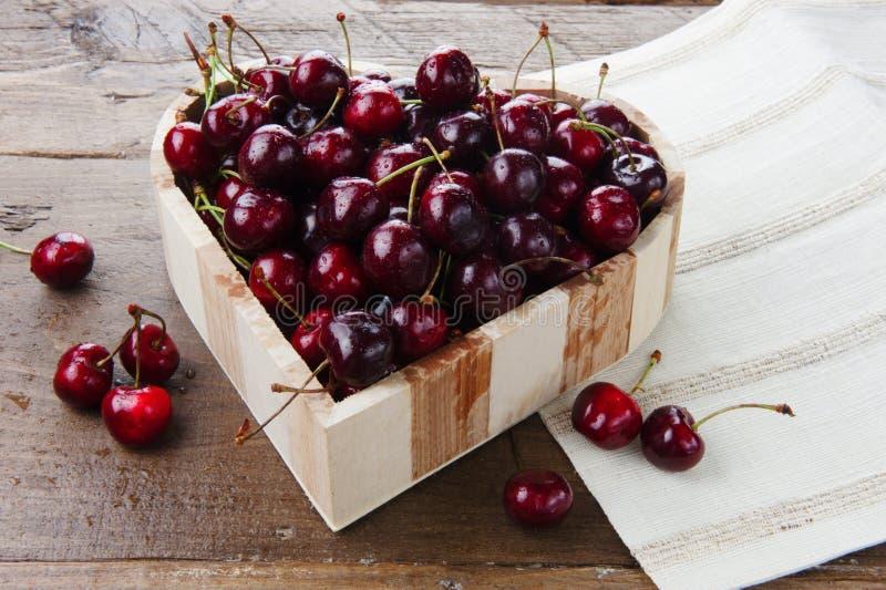 Fruit frais de cerise dans une cuvette en forme de coeur en bois photos libres de droits