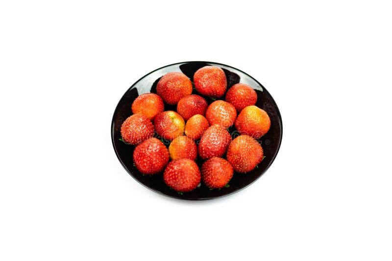 Fruit frais de fraise dans le plat noir d'isolement sur le fond blanc image stock