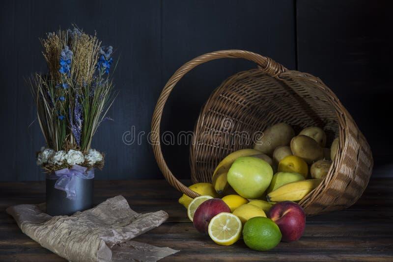 Fruit frais se renversant hors du panier D'obscurité toujours concept de la vie photo stock