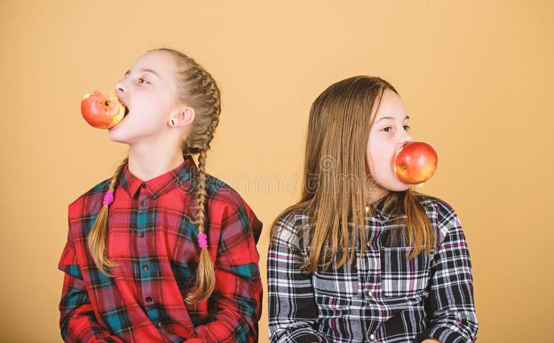 Fruit, fruit and more fruit. Little girls eating fresh fruits. Small girls holding apples in mouths. Cute children stock photos