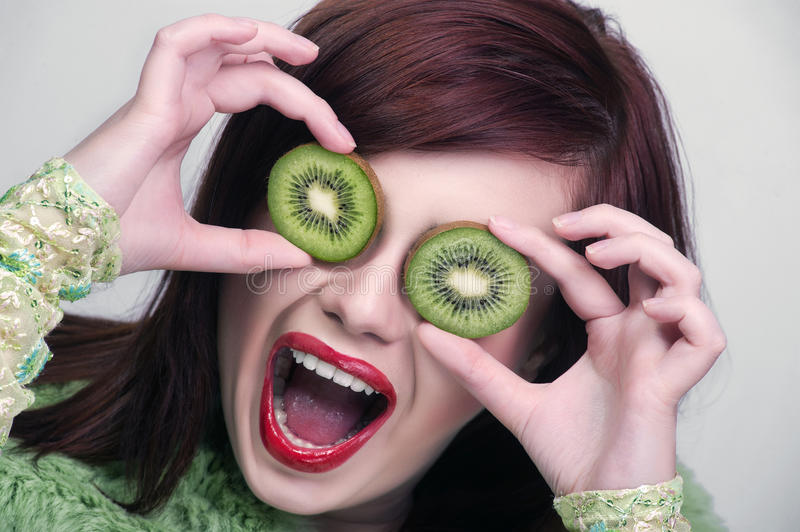 Fruit funny woman holding kiwi stock photos