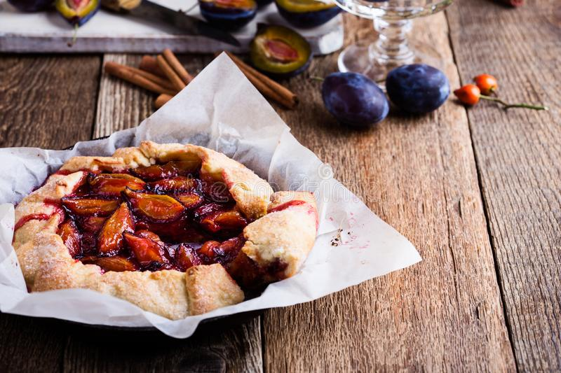 Homemade rustic plum tart, fruit galette. Fruit galette. Homemade rustic plum tart in cast iron skillet over country wooden background royalty free stock images