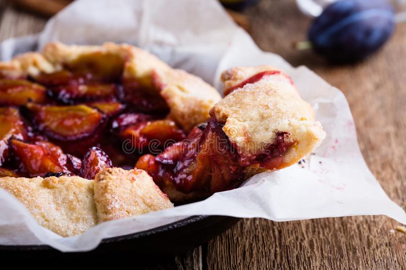 Homemade rustic plum tart, fruit galette. Fruit galette. Homemade rustic plum tart in cast iron skillet over country wooden background royalty free stock photos