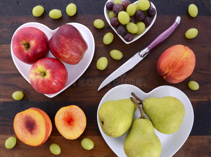 Fruit in heart shape plates on wood table. royalty free stock photography