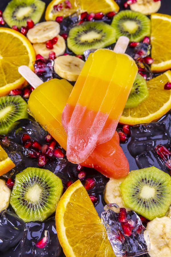 Fruit ice cream on stick with slices fruits stock photography