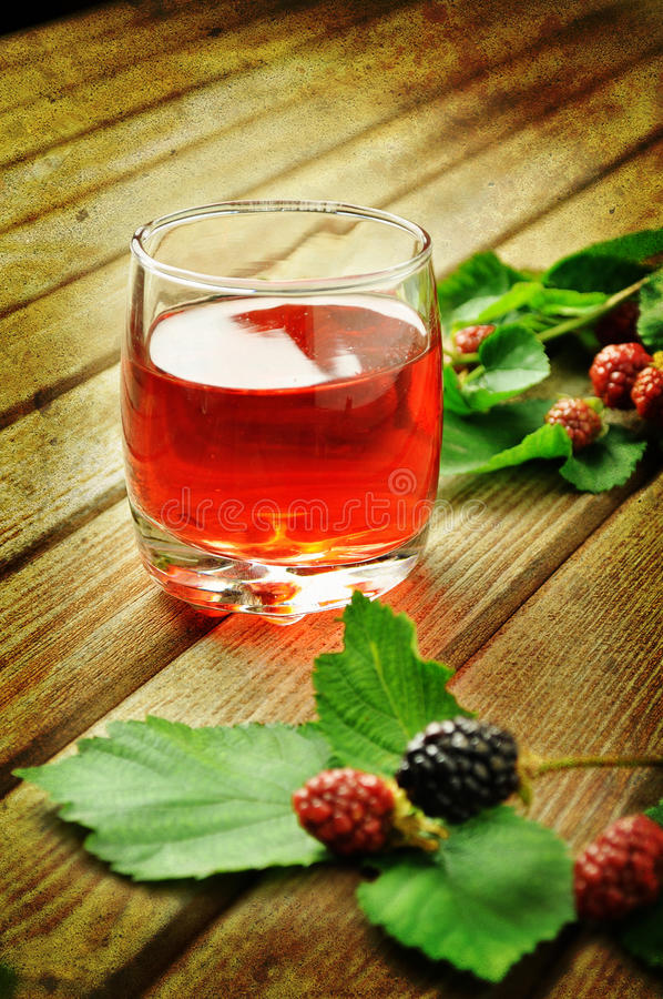 Fruit juice. Blackberry fruit juice on a rustic table royalty free stock image
