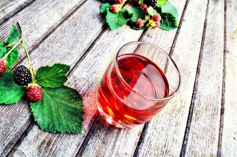 Fruit juice. Blackberry fruit juice on a rustic table stock image