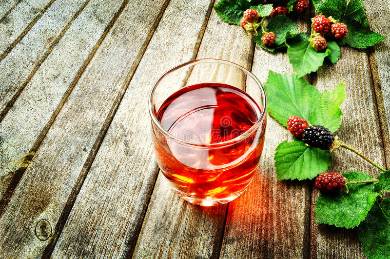 Fruit juice. Raspberry fruit juice on a rustic table royalty free stock images