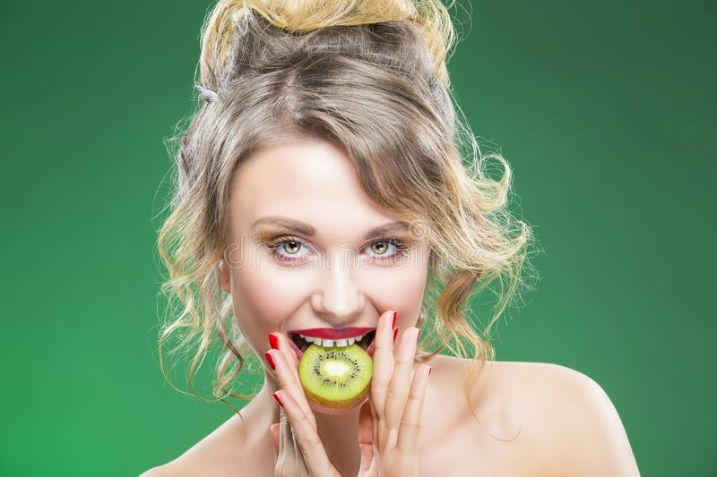 Fruit Kiwi Series. Sensual and Naked Caucasian Model. Fruit Series. Portrait of Curious Caucasian Blond Model Posing With Slice of Green Juicy Kiwi Fruit and Her stock photo
