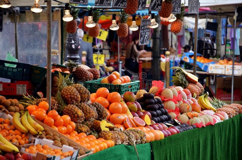 Fruit Market in Paris. Counters with bananas, oranges, pineapples, figs, coconuts, kiwi, grapefruit, melons, persimmons, mangoes royalty free stock photo