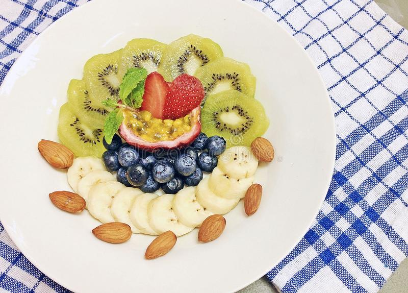 Fruit mixed with almonds yogurt. Kiwi,blueberries, strawberries, bananas and passion fruit mixed with almonds yogurt royalty free stock image