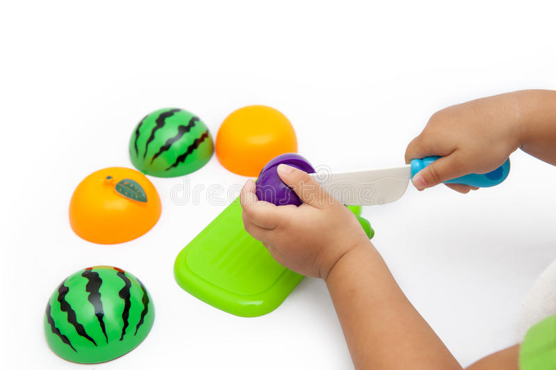 Fruit model. Little girl` s hand, playing the fruit model,toy royalty free stock photography