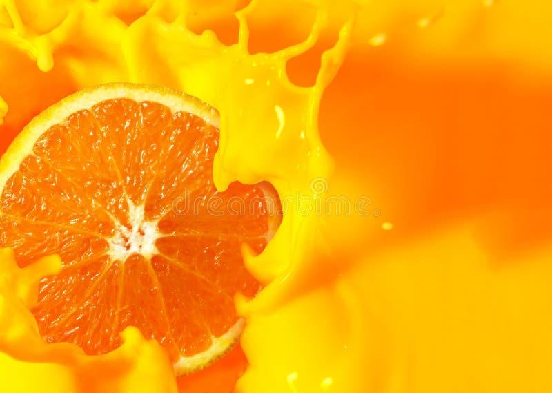 Fruit orange coupé en deux avec éclaboussure de jus d'orange photos libres de droits