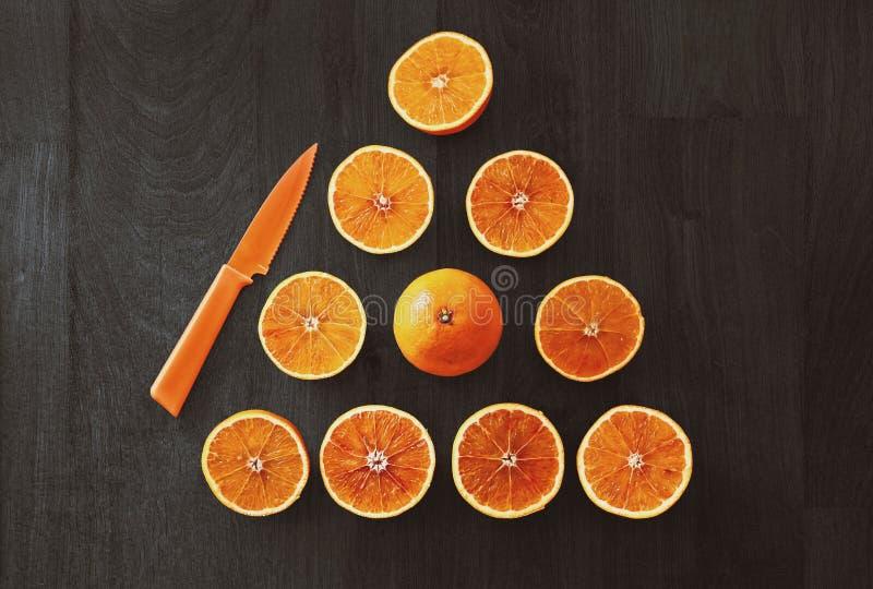 Fruit orange coupé en tranches avec le couteau photos stock