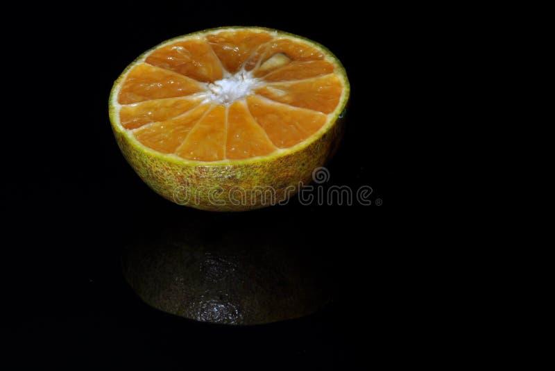 Fruit orange d'isolement sur le fond noir sain frais image libre de droits