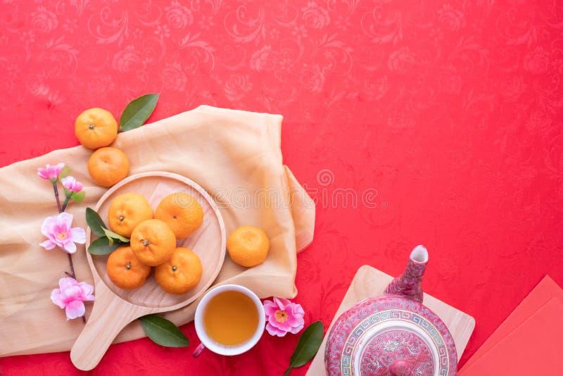 Fruit orange, fleurs de cerisier roses et théière avec l'espace de copie pour le texte sur le fond rouge de texture, concept de n image stock