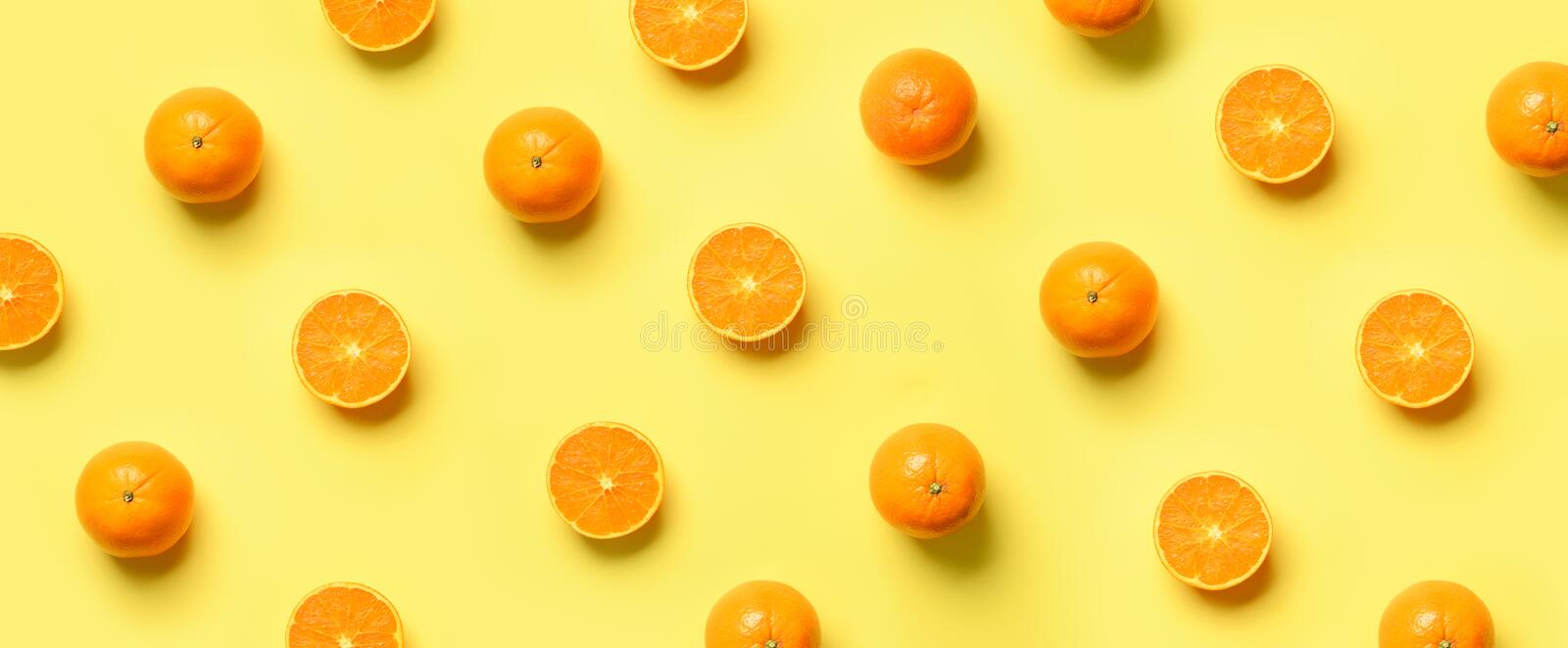 Fruit pattern of fresh orange slices on yellow background. Top view. Copy Space. Pop art design, creative summer concept. Half of. Citrus in minimal flat lay royalty free stock image