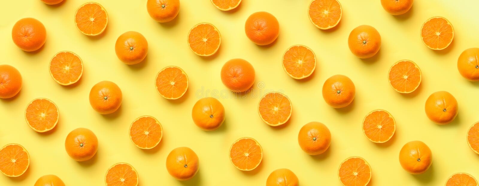 Fruit pattern of fresh orange slices on yellow background. Top view. Copy Space. Pop art design, creative summer concept. Half of. Citrus in minimal flat lay stock photography