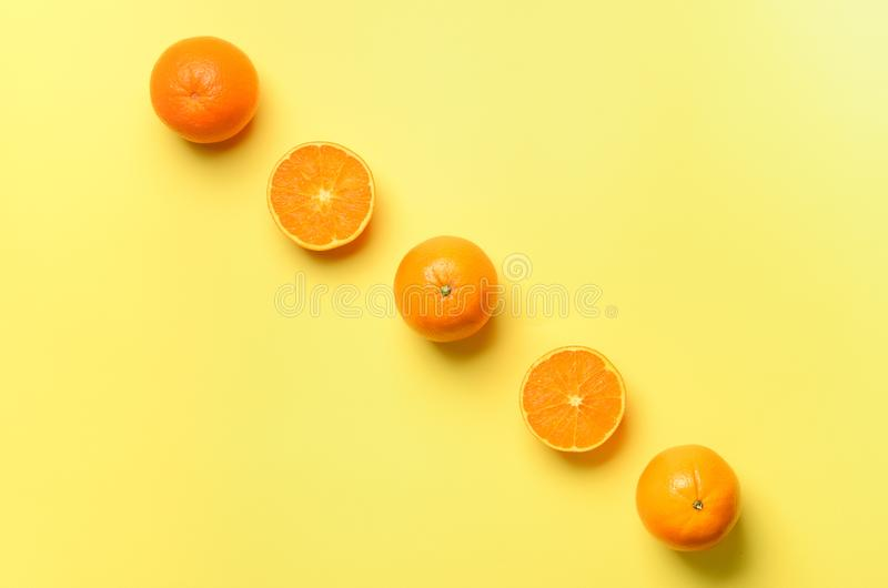Fruit pattern of fresh orange slices on yellow background. Top view. Copy Space. Pop art design, creative summer concept. Half of. Citrus in minimal flat lay stock image