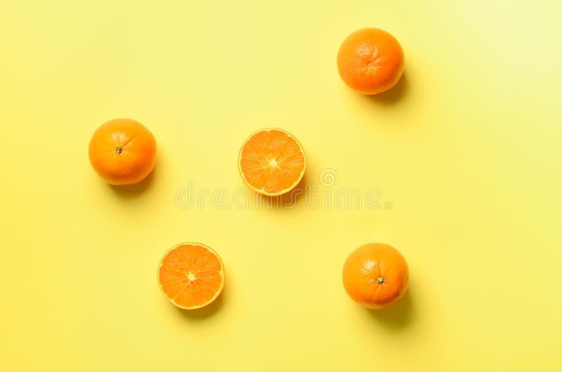 Fruit pattern of fresh orange slices on yellow background. Top view. Copy Space. Pop art design, creative summer concept. Half of. Citrus in minimal flat lay stock photo